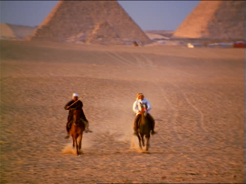vídeos y material grabado en eventos de stock de zoom out pan two bedouin men on horses running in desert with great pyramids in background / giza, egypt - herbívoro