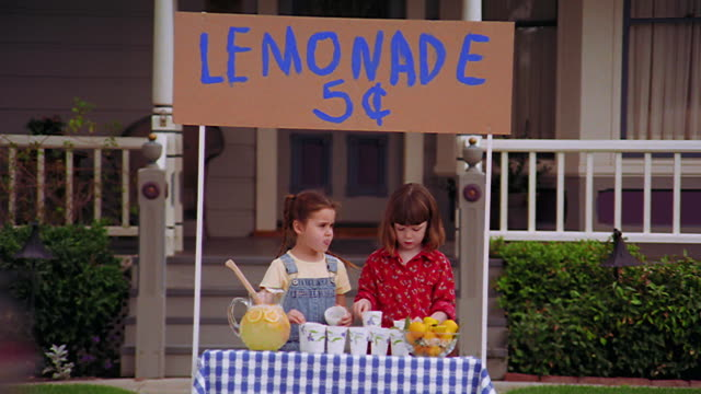 zoom out two girls lining up cups at lemonade stand in front of house - lemonade stock videos and b-roll footage