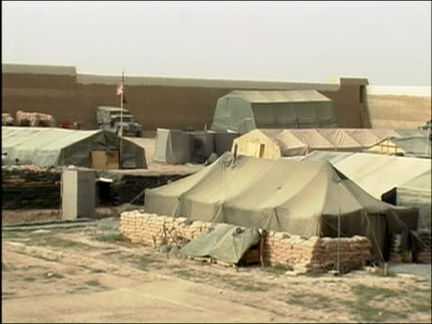 Zoom out view of US base camp with tents surrounded by stacks of sandbags / Ghazni Afghanistan