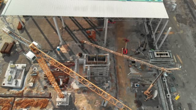 zoom out view over inactive cranes on the construction site - crane construction machinery stock videos & royalty-free footage
