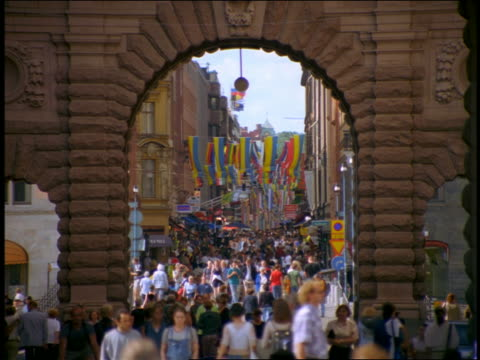 zoom out view thru archway of crowd walking on drottninggatan street / stockholm, sweden - stockholm stock videos & royalty-free footage