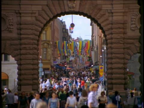 vídeos y material grabado en eventos de stock de zoom out view thru archway of crowd walking on drottninggatan street / stockholm, sweden - stockholm