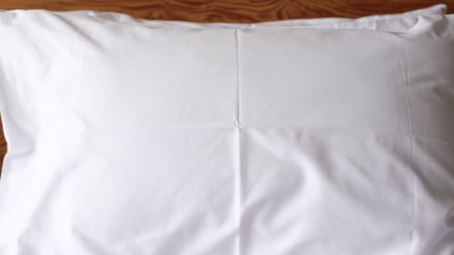zoom out white pillow on bed in bedroom - sheet stock videos & royalty-free footage