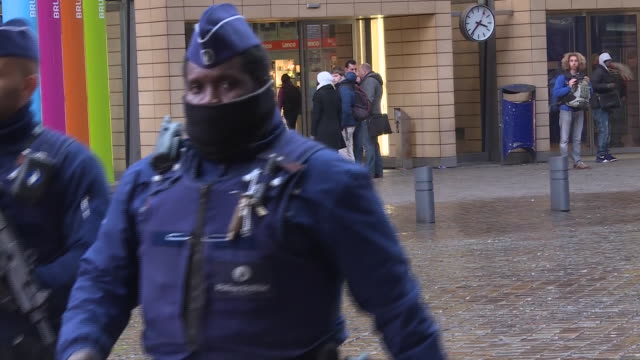 stockvideo's en b-roll-footage met zoom out wide shot of belgium policemen wearing uniforms and hats and holding guns as they walk outside the train station in brussels the heightened... - (war or terrorism or election or government or illness or news event or speech or politics or politician or conflict or military or extreme weather or business or economy) and not usa