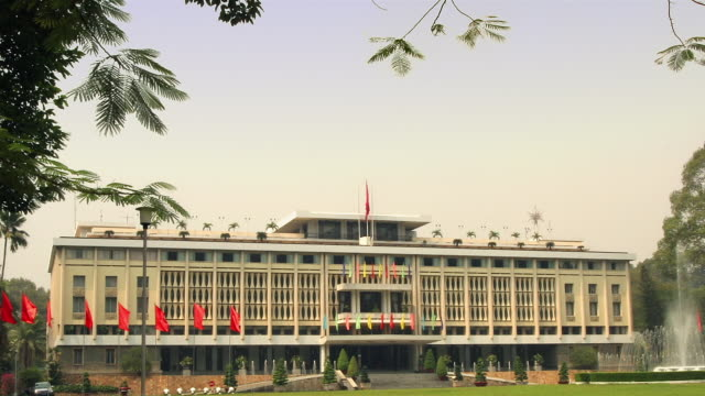 stockvideo's en b-roll-footage met zoom out wide shot reunification palace with vietnamese flags blowing in the wind / day / ho chi minh city, vietnam - communisme