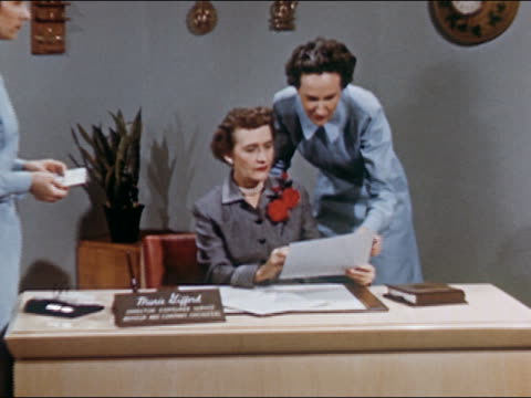 vidéos et rushes de 1951 zoom out wide shot women gathering around female boss's desk to read letter / boss getting up and leaving / audio - seulement des femmes