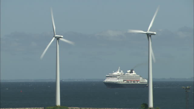 stockvideo's en b-roll-footage met zoom out windmills to cruise ship in denmark port - music or celebrities or fashion or film industry or film premiere or youth culture or novelty item or vacations