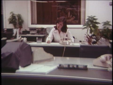 1970 zoom out woman alone in office at desk answers telephone - 1970 stock-videos und b-roll-filmmaterial