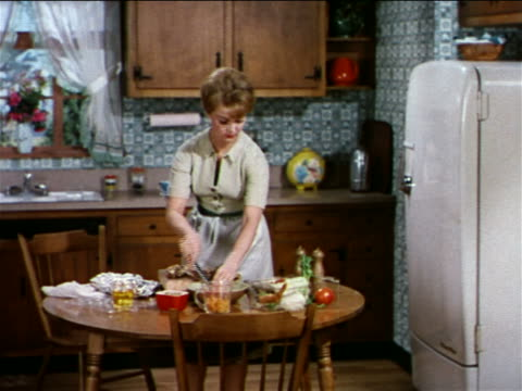 1962 zoom out woman in kitchen cutting meat on table with vegetables + mixing them together / industrial