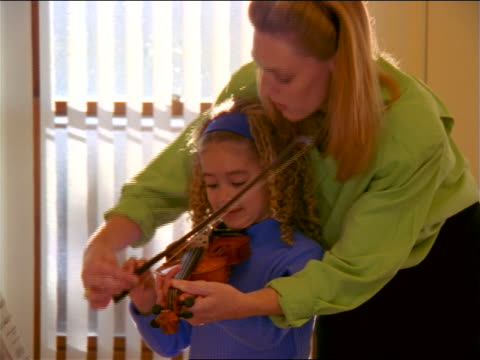 zoom out woman teaching young black girl how to use bow on violin near window - violin stock videos & royalty-free footage