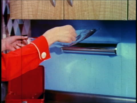 1955 zoom out woman tearing sheet from roll of aluminum foil + wrapping sandwich