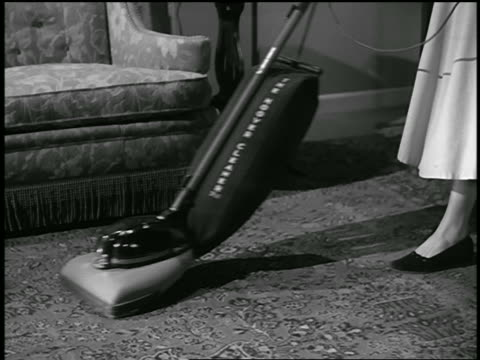 B/W 1945 zoom out woman vacuuming Oriental rug in living room with Hoover vacuum cleaner