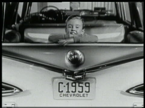 B/W 1959 zoom out young girl sitting in backseat of Chevrolet station wagon in showroom