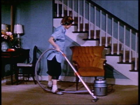 1952 zoom out young woman vacuuming in living room + talking to mother - 10 sekunden oder länger stock-videos und b-roll-filmmaterial