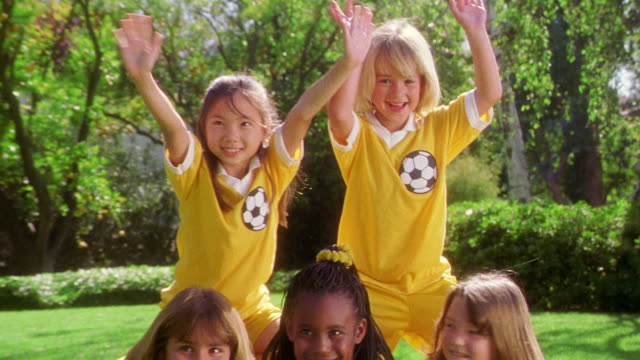 zoom out zoom in five girls in soccer uniforms form human pyramid by soccer ball / girls on top waving arms - human pyramid stock videos and b-roll footage