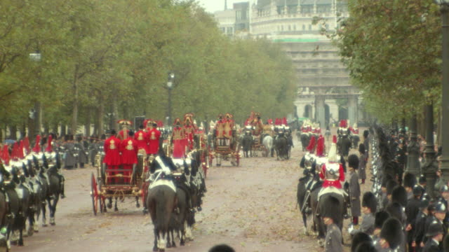 REAR VIEW zoom out zoom in royal carriages + royal guards (Household Cavalry) riding horses on street / London