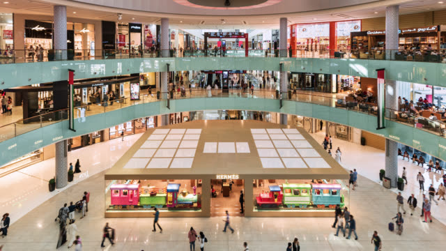 vidéos et rushes de tl/zo/pu zoom out/pan up time lapse of the main atrium inside dubai mall, busy with shoppers and visitors - zoom out