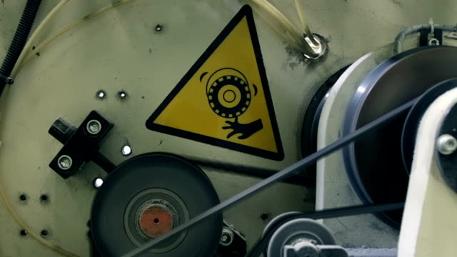 zoom: rotating machinery with a warning sign in a factory - pinching stock videos & royalty-free footage