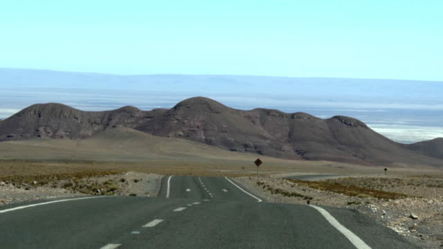 zoomed long and straight asphalt road while driving in the desert - san pedro de atacama stock videos & royalty-free footage