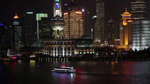 zoomed panning view of a boat on the huangpu river at night. - river huangpu stock videos & royalty-free footage