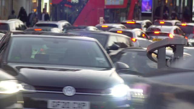 zoomed shot heavy london traffic at rush hour dusk cars passing camera traffic lights jam - traffic stock videos & royalty-free footage
