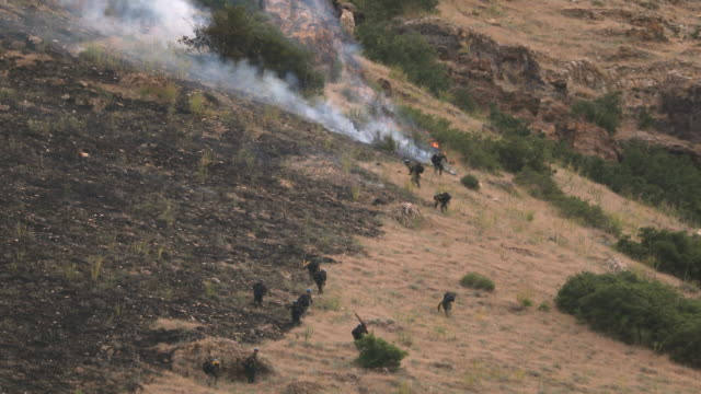 zoomed view of firefighters working to extinguish wildfire - provo stock-videos und b-roll-filmmaterial