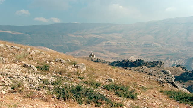 zoom-in of a christian shrine set in the arid expanse of the northern mount lebanon range. - christentum stock-videos und b-roll-filmmaterial
