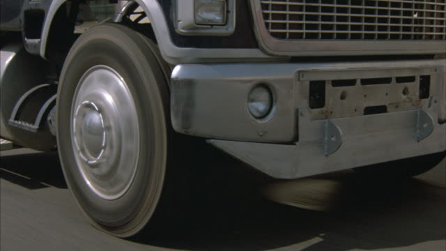 zoom-in on a semi's front-right wheel. - articulated lorry stock videos and b-roll footage