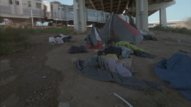 zoom-in on a tent under an overpass. - tent stock videos and b-roll footage
