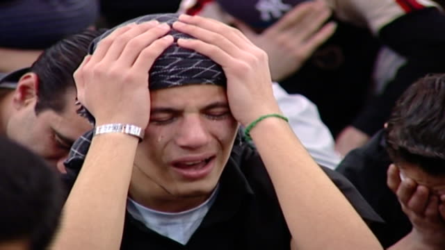 zoom-in on a young shia man overcome with emotion crying his eyes out, during ashura, a mourning rite commemorating the death of hussain ibn ali at... - シャイフ点の映像素材/bロール