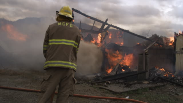 zoom-in past fireman in foreground to flaming ruins of a burned house - myrtle creek stock videos & royalty-free footage