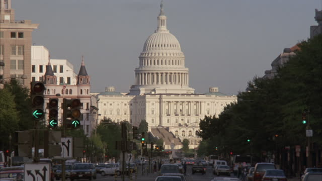 Zoom-in to U.S. Capitol Building dome as traffic moves toward the building.