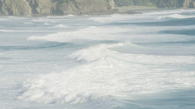 zooming in shot of waves at anawhata beach - coastal feature stock videos & royalty-free footage