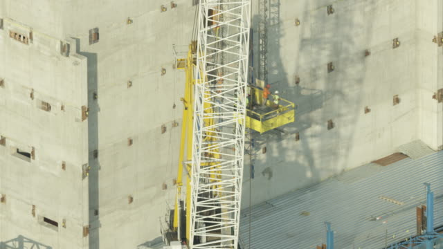Zooming in shot of workers on a construction platform