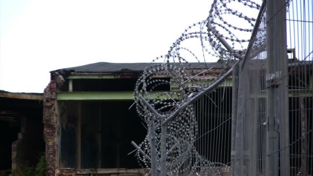 vídeos y material grabado en eventos de stock de zooming out alambradas, abandonado fábrica de fondo, hd - forbidden