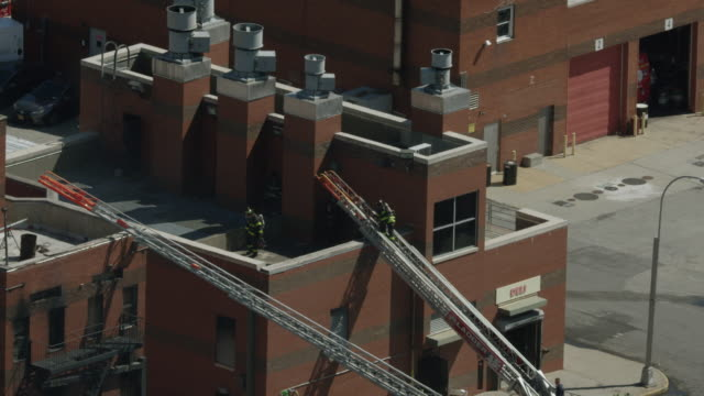 zooming out shot of a firefighter trainee climbing up from a ladder to a rooftop at the fire department of the city of new york training center - fire department of the city of new york stock videos and b-roll footage