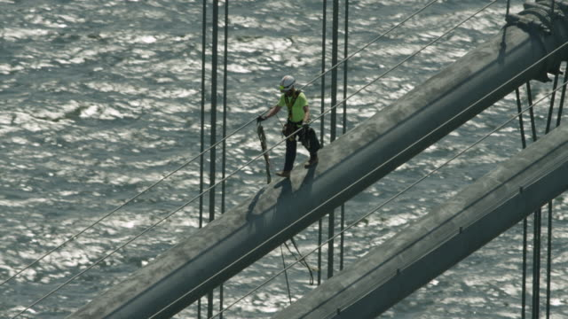 zooming out shot of a worker walking on the verrazano-narrows bridge main cable - baustelle stock-videos und b-roll-filmmaterial