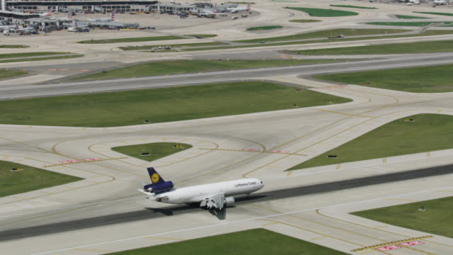 zooming out shot of an airplane slowing down on a runway of the o'hare international airport - taxiway stock videos & royalty-free footage