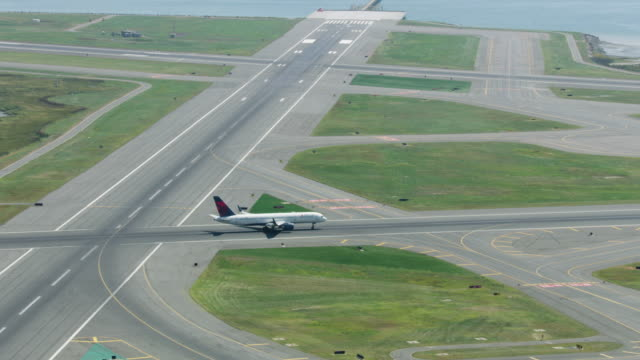 zooming out shot of an airplane taxiing on the runway of the logan international airport - taxiway stock videos & royalty-free footage