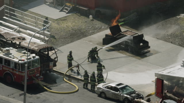 zooming out shot of firefighter trainees operating a fire hose on a burning car at the fire department of the city of new york training center - fire hose stock-videos und b-roll-filmmaterial