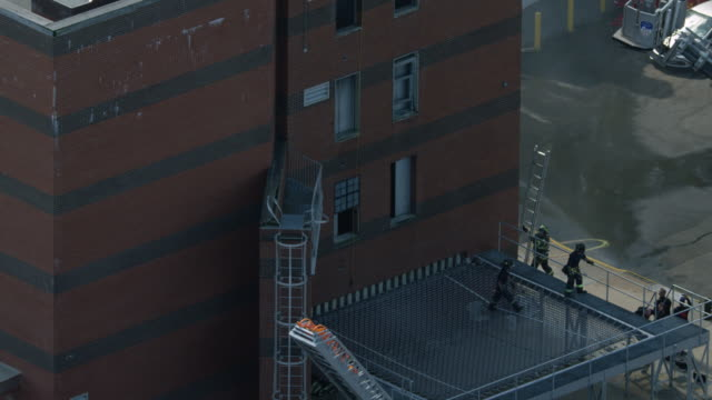 zooming out shot of firefighter trainees practicing at a smoking building and a simulated container ship at the fire department of the city of new york training center - fire department of the city of new york stock videos and b-roll footage