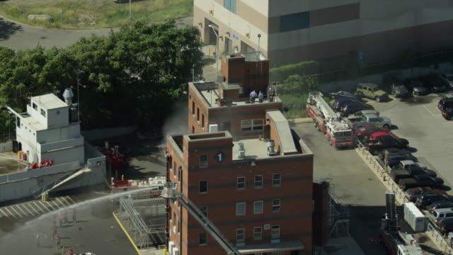 zooming out shot of firefighter trainees practicing on the roof of a smoking building and a simulated container ship at the fire department of the city of new york training center - fire department of the city of new york stock videos and b-roll footage
