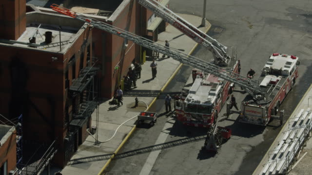zooming out shot of firefighter trainees standing next to a building and ladder trucks at the fire department of the city of new york training center - fire department of the city of new york stock videos and b-roll footage