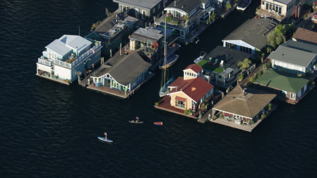 vídeos de stock e filmes b-roll de zooming out shot of floating homes on lake union - barco casa
