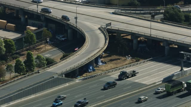 zooming out shot of homeless shacks along the dwight d eisenhower highway under the overpass of the university avenue - povertà video stock e b–roll