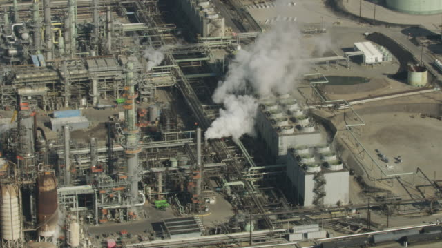 Zooming out shot of spinning rooftop turbines in the Chevron El Segundo Refinery