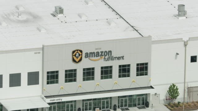 zooming out shot of the sign on the amazon warehouse - logo stock-videos und b-roll-filmmaterial