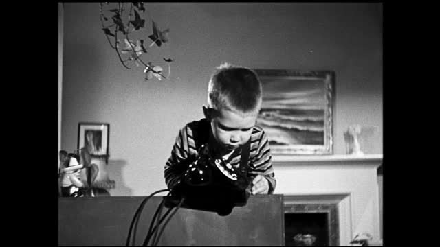 zooming out view of internal components of a telephone laid out on display; little boy slowly pushes telephone off the table - 1940 1949 video stock e b–roll