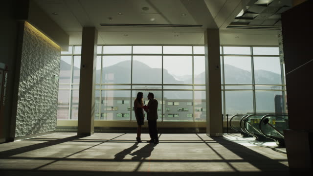Zooming shot of silhouetted business shaking hands and walking apart in lobby / Provo, Utah, United States,