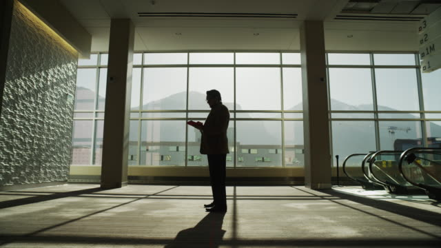 Zooming shot of silhouetted businessman using digital tablet in lobby / Provo, Utah, United States,